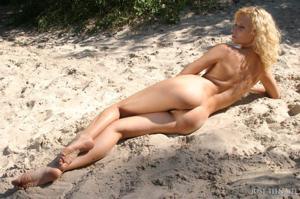 На пустом берегу блондинка лежит на песочке - фото #6