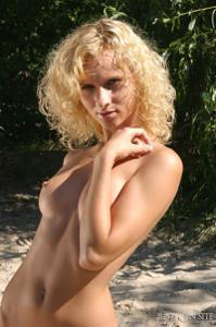 На пустом берегу блондинка лежит на песочке - фото #8