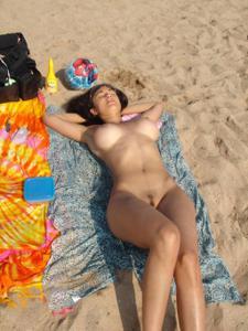Классная брюнетка загорает голой на пляже