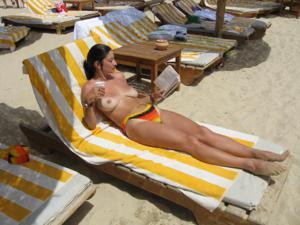 Грудастая девушка позирует дома на кровати и на пляже - фото #16