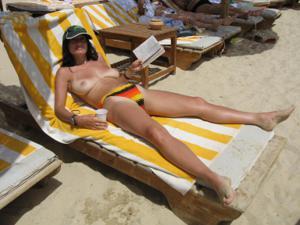 Грудастая девушка позирует дома на кровати и на пляже - фото #30