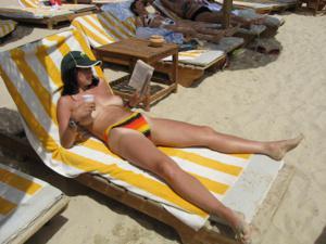 Грудастая девушка позирует дома на кровати и на пляже - фото #31