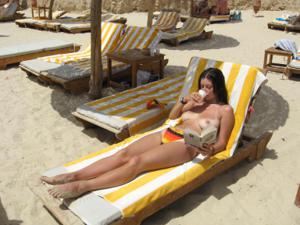 Грудастая девушка позирует дома на кровати и на пляже - фото #33