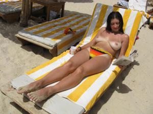 Грудастая девушка позирует дома на кровати и на пляже - фото #34