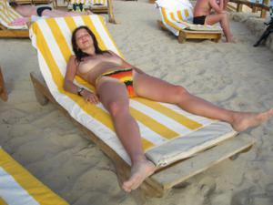 Грудастая девушка позирует дома на кровати и на пляже - фото #46