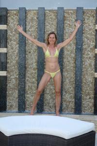 Зрелая женщина позирует в прозрачном купальнике желтого цвета - фото #11