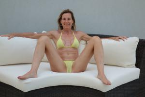 Зрелая женщина позирует в прозрачном купальнике желтого цвета - фото #16