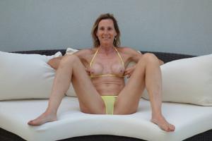 Зрелая женщина позирует в прозрачном купальнике желтого цвета - фото #17