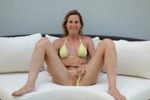 Зрелая женщина позирует в прозрачном купальнике желтого цвета - фото #18