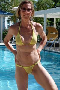 Зрелая женщина позирует в прозрачном купальнике желтого цвета - фото #22