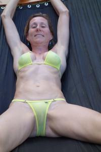 Зрелая женщина позирует в прозрачном купальнике желтого цвета - фото #26