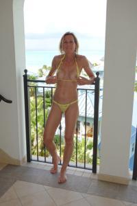 Зрелая женщина позирует в прозрачном купальнике желтого цвета - фото #32