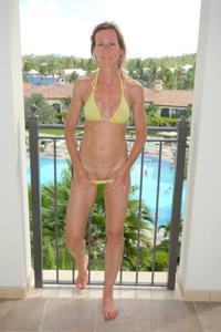 Зрелая женщина позирует в прозрачном купальнике желтого цвета - фото #36