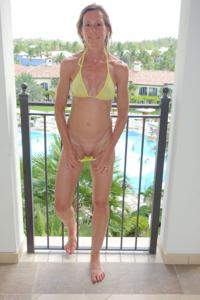Зрелая женщина позирует в прозрачном купальнике желтого цвета - фото #37