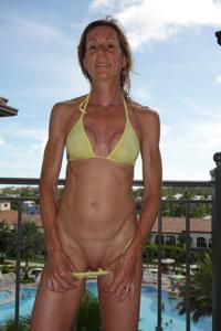Зрелая женщина позирует в прозрачном купальнике желтого цвета - фото #38