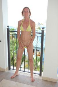 Зрелая женщина позирует в прозрачном купальнике желтого цвета - фото #39