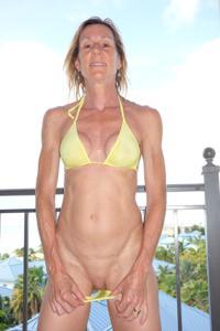 Зрелая женщина позирует в прозрачном купальнике желтого цвета