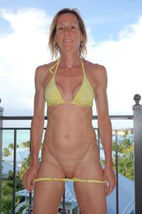 Зрелая женщина позирует в прозрачном купальнике желтого цвета - фото #43