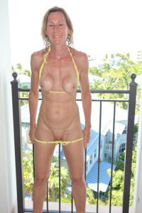 Зрелая женщина позирует в прозрачном купальнике желтого цвета - фото #45