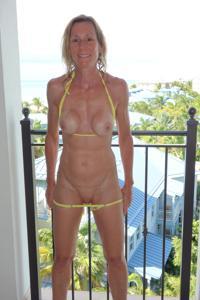Зрелая женщина позирует в прозрачном купальнике желтого цвета - фото #46