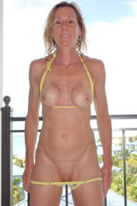 Зрелая женщина позирует в прозрачном купальнике желтого цвета - фото #48