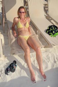 Зрелая женщина позирует в прозрачном купальнике желтого цвета - фото #53