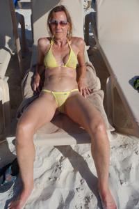 Зрелая женщина позирует в прозрачном купальнике желтого цвета - фото #54