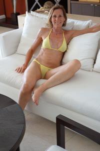 Зрелая женщина позирует в прозрачном купальнике желтого цвета - фото #6