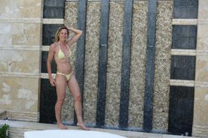 Зрелая женщина позирует в прозрачном купальнике желтого цвета - фото #9
