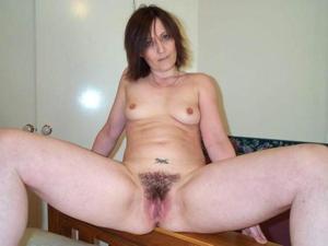 Зрелая женщина показывает мохнатку раздвигая ноги - фото #7